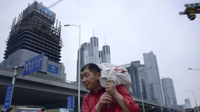 A man carries a package as he walks along a street at in Beijing's central business district