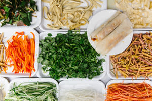 Ready to eat spring rolls in a plate next to a wide choise of vegetables available for a filling mix.