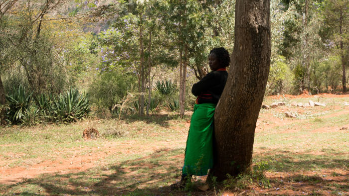 Wayu Kisilu stands off to the side as the women's group discusses the possibility to giving her a new loan during a meeting in Kyangala, Kenya, November 15, 2018.
