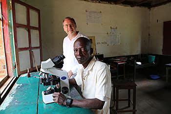 Piot with Sukato Mandzomba in the latter's makeshift laboratory in Yambuku