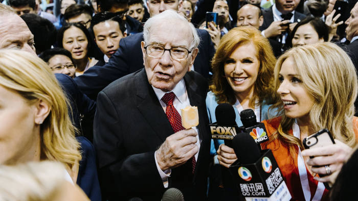 Warren Buffett, chairman and chief executive officer of Berkshire Hathaway Inc., center left, eats a Dairy Queen vanilla orange ice cream bar while touring the shopping floor ahead of the company's annual meeting in Omaha, Nebraska, U.S., on Saturday, May 4, 2019. Buffett's Berkshire Hathaway agreed earlier this week to make the investment in Occidental to help the oil producer with its $38 billion bid for Anadarko Petroleum Corp. Photographer: Houston Cofield/Bloomberg