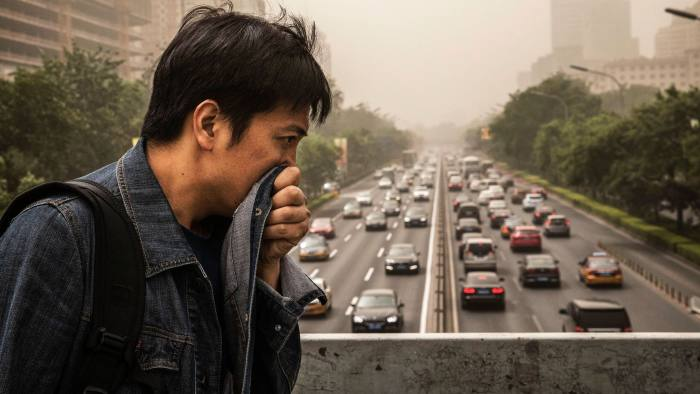 BEIJING, CHINA - MAY 04: A Chinese man covers his mouth and nose with his jacket to try and protect from particles blown in during a sandstorm as he walks in the street on May 4, 2017 in Beijing, China. Sandstorms are common in northern China during the spring season and are caused when heavy winds from Mongolia in the north brings sand and pollutants that can blanket Chinese cities and cause air quality to deteriorate. (Photo by Kevin Frayer/Getty Images)