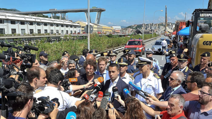 Italian Deputy Premier Luigi Di Maio, center right, and Italian Transport and Infrastructure Minister Danilo Toninelli, center left with glasses, speak to the media in front of the collapsed Morandi highway bridge in Genoa, northern Italy, Wednesday, Aug. 15, 2018. A bridge on a main highway linking Italy with France collapsed in the Italian port city of Genoa during a sudden, violent storm, sending vehicles plunging 90 meters (nearly 300 feet) into a heap of rubble below. (Alessandro Di Marco/ANSA via AP)