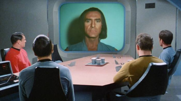 """LOS ANGELES - FEBRUARY 16: on screen is Ricardo Montalban as Khan Noonien Singh (a genetically engineered human from the 20th century). At table from left is James Doohan as Lt. Commander Montgomery Scotty Scott, Leonard Nimoy as Commander Spock (Mr. Spock), William Shatner as Captain James T. Kirk and DeForest Kelley as Dr. Bones McCoy in the Star Trek: The Original Series episode, """"Space Seed."""" Original air date February 16, 1967. Image is a frame grab. (Photo by CBS via Getty Images)"""