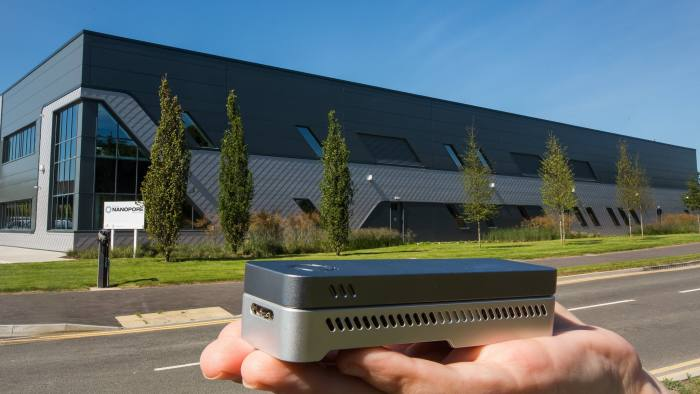 Oxford Nanopore's new factory on Harwell science campus in the background, with one of its MinIon DNA readers in the foreground.