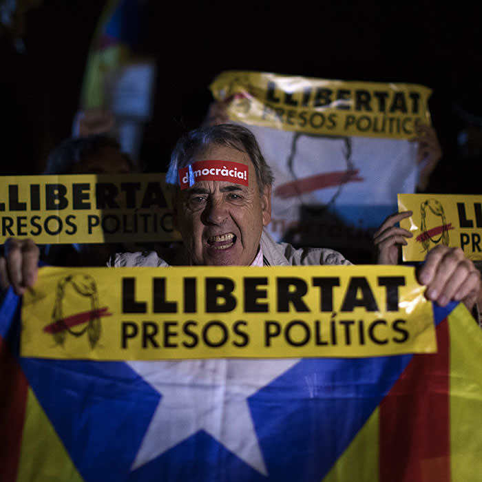 """Demonstrators holding banners reading in Catalan """"freedom for the political prisoners"""" gather outside the Catalonian Parliament to protest against the decision of a judge to jail ex-members of the Catalan government, in Barcelona, Spain, Thursday, Nov. 2, 2017. A Spanish judge has ordered nine ex-members of the government in Catalonia jailed while they are investigated on possible charges of sedition, rebellion and embezzlement. (AP Photo/Emilio Morenatti)"""