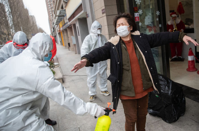 TOPSHOT - A woman (R), who has recovered from the COVID-19 coronavirus infection, is disinfected by volunteers as she arrives at a hotel for a 14-day quarantine after being discharged from a hospital in Wuhan, in China's central Hubei province on March 1, 2020. - China on March 1 reported 35 more deaths from the new coronavirus, taking the toll in the country to 2,870. (Photo by STR / AFP) / China OUT (Photo by STR/AFP via Getty Images)