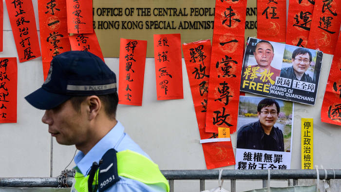 "Police walk past messages in support of jailed Chinese human rights lawyer Wang Quanzhang (pictured R on placard) and China's first ""cyber-dissident"" and founder of human rights website ""64 Tianwang"", Huang Qi (pictured L on placard), after a protest attended by Hong Kong pro-democracy activists outside the Chinese Liaison Office in Hong Kong on January 29, 2019. - Prominent Chinese human rights lawyer Wang Quanzhang was sentenced on January 28 to four and a half years in prison for state subversion, sealing the fate of another attorney swept up in a 2015 crackdown. (Photo by Anthony WALLACE / AFP) (Photo credit should read ANTHONY WALLACE/AFP/Getty Images)"