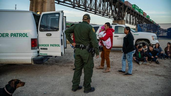 A group of about 30 Brazilian migrants, who had just crossed the border, get into a US Border Patrol van, taking them off the property of Jeff Allen, who used to run a brick factory near Mt. Christo Rey on the US-Mexico border in Sunland Park, New Mexico on March 20, 2019. - The militia members say they will patrol the US-Mexico border near Mt. Christo Rey,
