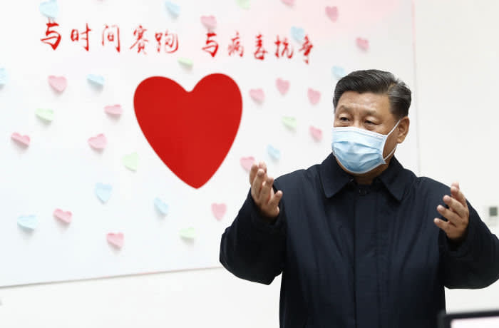 "In this Feb. 10, 2020, photo released by Xinhua News Agency, Chinese President Xi Jinping gestures near a heart shape sign and the slogan ""Race against time, Fight the Virus"" during an inspection of the center for disease control and prevention of Chaoyang District in Beijing. China's daily death toll from a new virus topped 100 for the first time and pushed the total past 1,000 dead, authorities said Tuesday after leader Xi Jinping visited a health center to rally public morale amid little sign the contagion is abating. (Liu Bin/Xinhua via AP)"