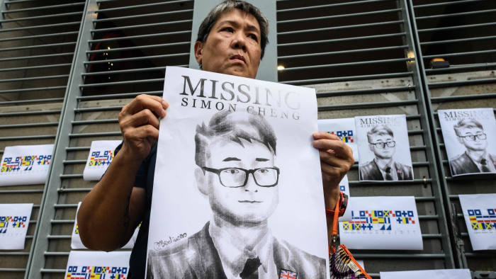 An activist holds an illustration of Simon Cheng during a gathering outside the British Consulate-General building in Hong Kong on August 21, 2019, following reports that the Hong Kong consulate employee had been detained by mainland Chinese authorities on his way back to the city. - An employee of Britain's consulate in Hong Kong who went missing earlier this month is being held in China, Beijing confirmed on August 21. (Photo by Anthony WALLACE / AFP)ANTHONY WALLACE/AFP/Getty Images
