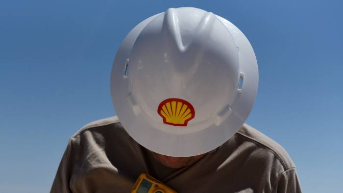 """A logo is displayed on the hardhat of a worker at the Royal Dutch Shell Plc processing facility in Loving, Texas, U.S., on Friday, Aug. 24, 2018. Royal Dutch Shell Plccame through a quarter of volatile oil prices to beat earnings estimates, delivering a surge in cash flow the company said will underpin """"world-class"""" returns to investors. Photographer: Callaghan O'Hare/Bloomberg"""
