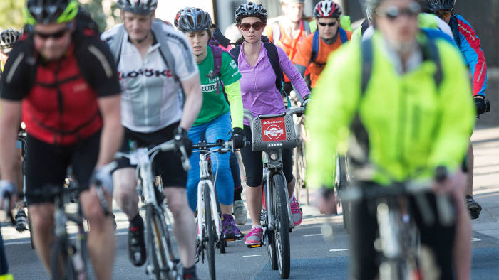 """A cyclist rides a London cycle hire bicycle, sponsored by Santander UK Plc, also known as a """"Boris bike"""", center, along a section of the Cycle Superhighway 8 (CS8) in London, U.K., on Wednesday, April 22, 2015"""