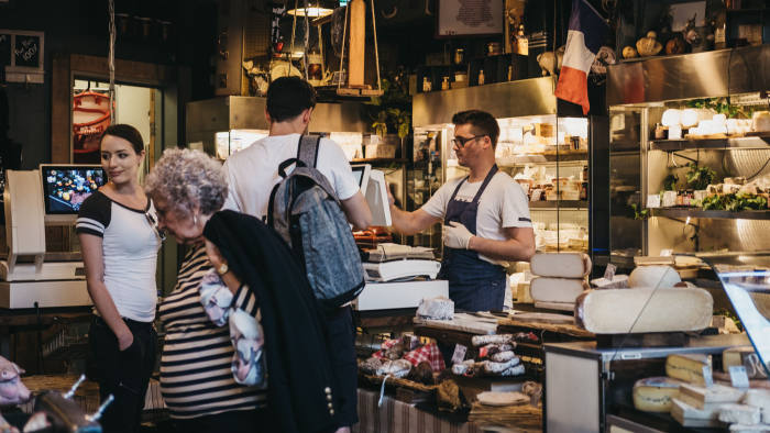 London, UK - September 17, 2018: Seller and customers inside charcuterie and cheese stand in Borough Market, one of the largest and oldest food markets in London.
