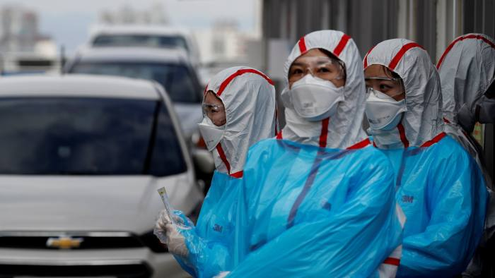 FILE PHOTO: Medical staff in protective gear work at a 'drive-thru' testing center for the novel coronavirus disease of COVID-19 in Yeungnam University Medical Center in Daegu, South Korea, March 3, 2020. To match Special Report HEALTH-CORONAVIRUS/RESPONSE REUTERS/Kim Kyung-Hoon/File Photo