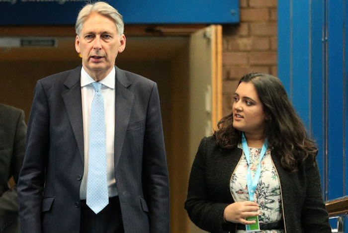 Chancellor Philip Hammond walks with Sonia Khan as he arrives at the Conservative Party annual conference at the International Convention Centre, Birmingham in October 2018 .