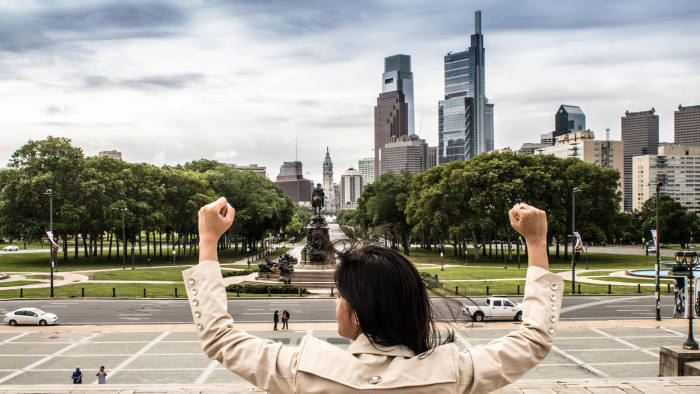 PAEFHY A young woman flexing and imitating the famous Rocky pose as a symbol of women empowerment - Rocky Steps, The Oval, Philadelphia, USA