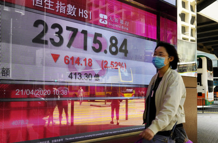 A woman wearing face mask walks past a bank electronic board showing the Hong Kong share index at Hong Kong Stock Exchange Tuesday, April 21, 2020. Asian shares skidded on Tuesday after U.S. oil futures plunged below zero as storage for crude runs close to full amid a worldwide glut as demand collapses due to the pandemic. (AP Photo/Vincent Yu)