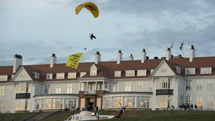 """A Greenpeace protester flying a paraglider passes over Donald Trump's resort in Turnberry, South Ayrshire, with a banner reading """"Trump: Well Below Par"""", shortly after the US President arrived at the hotel. PRESS ASSOCIATION Photo. Picture date: Friday July 13, 2018. See PA story POLITICS Trump. Photo credit should read: John Linton/PA Wire"""