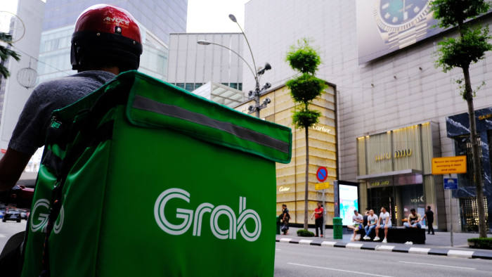 A Grab Holdings Inc. driver waits for an order in the Bukit Bintang district of Kuala Lumpur, Malaysia, on Monday, Jan. 6, 2020. Ringgit is poised for its first advance in three sessions, after overseas investors scooped up Malaysian stocks and the risk-off mood in global markets eased. Photographer: Samsul Said/Bloomberg