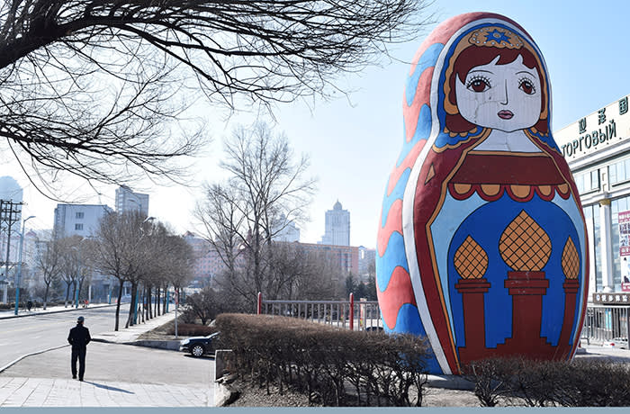 FILE PHOTO: A man walks past a giant statue of a Russian Matryoshka doll on a street in Suifenhe, China, a city in Heilongjiang province on the border with Russia April 12, 2020. REUTERS/Huizhong Wu/File Photo - RC266G9SEMJT