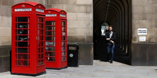 A pedestrian walks past red public telephone boxes near the Town Hall polling station in the European Union (EU) referendum in Manchester, U.K., on Thursday, June 23, 2016. Britain began voting Thursday on whether to remain a member of the European Union or split from the 28-nation bloc, a once-in-a-generation decision that will determine the U.K.'s future economic prosperity and the course of the EU. Photographer: Simon Dawson/Bloomberg