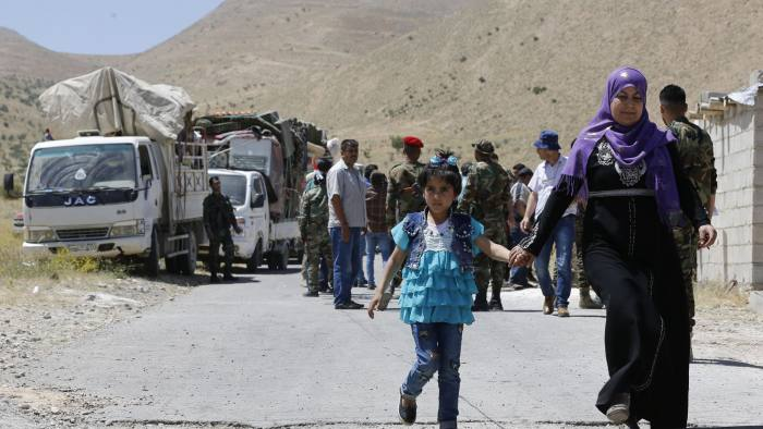 Syrian refugees arriving in their country from the eastern Lebanese border town of Arsal, walk through the crossing of al-Zamrani between the two countries on June 28, 2018. Syrian refugees arriving in their country from Lebanon walk through the border crossing of al-Zamrani between the two countries on June 28, 2018. / AFP PHOTO / LOUAI BESHARALOUAI BESHARA/AFP/Getty Images
