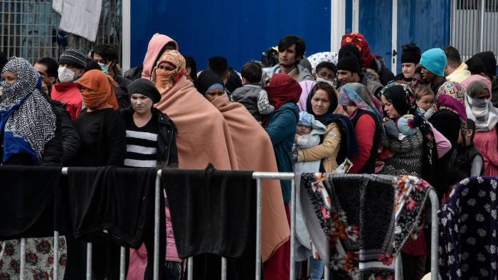Migrants and refugess who arrived from Turkey to the island of Lesbos queue for food at the port of Mytilene where they camp, while waiting to board a Navy carrier on the island of Lesbos on March 5, 2020. (Photo by LOUISA GOULIAMAKI / AFP) (Photo by LOUISA GOULIAMAKI/AFP via Getty Images)