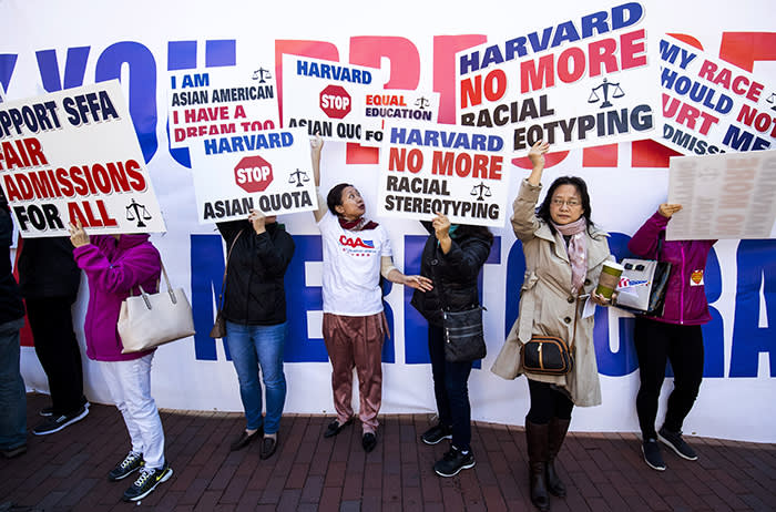 Demonstrators against Harvard University's admission process hold signs while gathering during a protest against Harvard University's admission process at Copley Square in Boston, Massachusetts, U.S., on Sunday, Oct. 14, 2018. Harvard University was sued by a group that claims their law school illegally used race and gender as criteria for selecting law students to staff their most elite academic journals, a suit that comes amid growing scrutiny of affirmative action in college admissions. Photographer: Adam Glanzman/Bloomberg