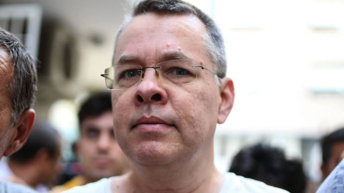 (FILES) In this file photo taken on July 25, 2018 US pastor Andrew Craig Brunson is escorted by Turkish plainclothes police officers to his house on in Izmir. The United States on August 1, 2018 hit two top Turkish officials with sanctions over the ongoing detention of an American pastor facing terror charges, heaping pressure on Ankara to release the prisoner fueling a bitter diplomatic feud.The move targeting Justice Minister Abdulhamit Gul and Interior Minister Suleyman Soylu further ratcheted up tensions between the NATO allies, and comes after President Recep Tayyip Erdogan insisted his government would not give in to Washington's threats.Andrew Brunson, who led a Protestant church in the Aegean city of Izmir, was placed under house arrest last week after nearly two years in jail on charges of espionage and supporting terror groups. He faces up to 35 years in jail if convicted. / AFP PHOTO / --/AFP/Getty Images