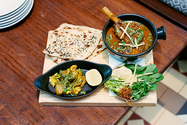 Dishoom's Nalli Nihari lamb stew, served with a plate of mint, fresh ginger, green chilli, coriander, onion and lemon, Bheja (lamb's brains) and a sesame-onion-seed naan
