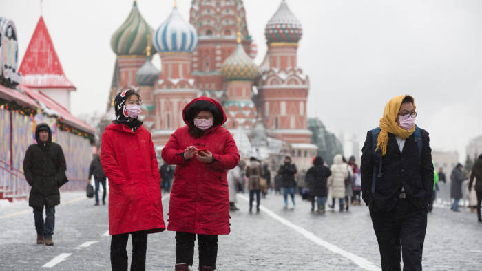 Tourists wear protective face masks as they walk in Red Square near the Kremlin in Moscow, Russia, on Tuesday, Jan. 28, 2020. The outbreak of the deadly coronavirus threatens to derail a fragile stabilization in the world economy, which had appeared poised to benefit from the phase one U.S.-China trade deal, and signs of a tech turnaround. Photographer: Andrey Rudakov/Bloomberg