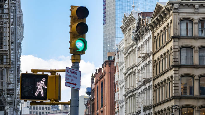 Traffic light and old buildings at an intersection on Broome Street in the SoHo neighborhood in Manhattan New York City