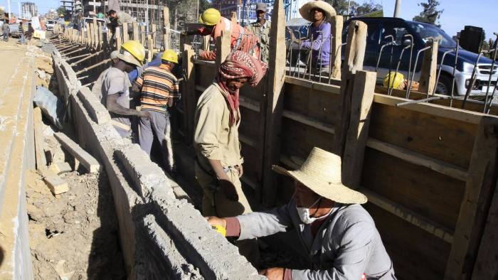 A Chinese contractor and local labourers works at a Metro-line station in Ethiopia's capital Addis Ababa February 7, 2015. Chinese workers mingle with Ethiopians putting the finishing touches to a city metro line that cuts through Addis Ababa, one of a series of grand state infrastructure projects that Ethiopia hopes will help it mimic Asia's industrial rise. To match Insight ETHIOPIA-ECONOMY/. Picture taken February 7, 2015. REUTERS/Tiksa Negeri (ETHIOPIA - Tags: BUSINESS CONSTRUCTION TRANSPORT) - RTR4OO78