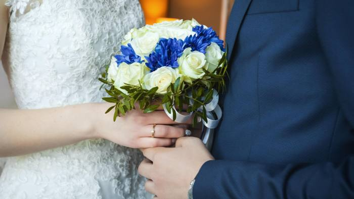 KFJCF8 Groom with bride holding wedding bouquet