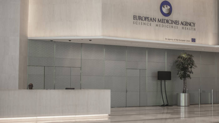A lone security guard sits behind the reception desk at the European Medicines Agency's deserted offices in London