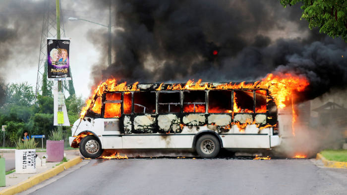 FILE PHOTO: A burning bus, set alight by cartel gunmen to block a road, is pictured during clashes with federal forces following the detention of Ovidio Guzman, son of drug kingpin Joaquin