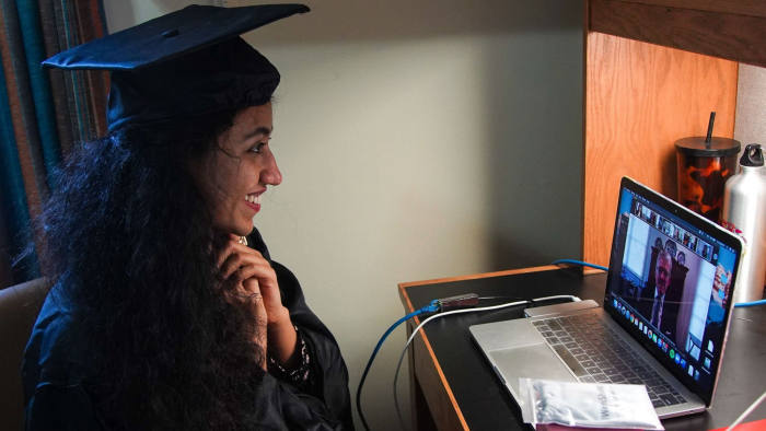 Pakistani student Varsha Thebo, 27, attends her online graduation ceremony in her bedroom at the International Student House where she resides at Georgetown University, in Washington, DC on May 15, 2020. - Varsha studied Global Human Development, her graduation ceremony was cancelled due to the coronavirus pandemic, so she is celebrating online instead. (Photo by Agnes BUN / AFP) (Photo by AGNES BUN/AFP via Getty Images)
