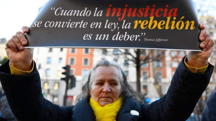 """A woman holds a sign reading """"When injustice becomes law, rebellion is a must"""" during a protest against the trial of jailed Catalan separatists at the Supreme Court in Madrid on February 12, 2019. - Twelve former Catalan leaders go on trial at Spain's Supreme Court for their role in a failed 2017 bid to break away from Spain. (Photo by GABRIEL BOUYS / AFP)GABRIEL BOUYS/AFP/Getty Images"""