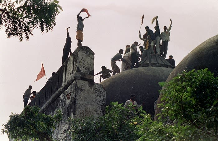 """In this file photograph taken on December 6, 1992 Hindu youths clamour atop the 16th century Muslim Babri Mosque five hours before the structure was completely demolished by hundreds supporting Hindu fundamentalist activists. - An inquiry into the demolition of a mosque that led to bloody Hindu-Muslim riots in India will accuse senior Hindu nationalist politicians of orchestrating the destruction, a report said on November 23, 2009. The Bharatiya Janata Party (BJP) party stalled business in parliament over claims in the Indian Express newspaper that an official probe into the razing of the 16th-century Babri Mosque in 1992 """"indicted"""" the party's leaders. AFP PHOTO/DOUGLAS E CURRAN/FILES (Photo credit should read DOUGLAS E. CURRAN/AFP/Getty Images)"""
