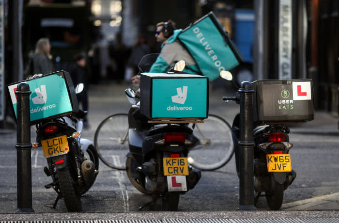 A food delivery cycle courier, working for Deliveroo, operated by Roofoods Ltd., passes motor scooters with boxes for Deliveroo, left and center, and UberEats, operated by Uber Technologies Inc., right, in London, U.K., on Thursday, Dec. 22, 2016. The food delivery business model has proven attractive to venture capitalists, who last year poured $5.5 billion into food-delivery companies globally, according to research firm CB Insights. Photographer: Simon Dawson/Bloomberg