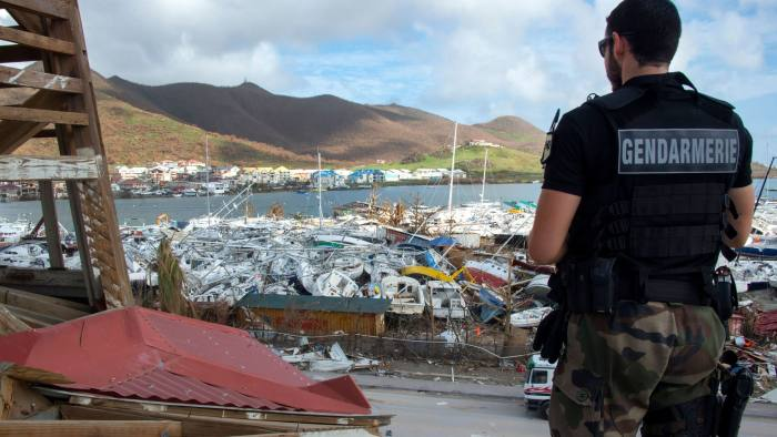 A gendarme stands in front of smashed boats on September 16, 2017 at Marigot shipyard on the French Caribbean island of Saint Martin after the island was hit by Hurricane Irma. The Caribbean island of St Martin was a place of spectacular inequalities before Hurricane Irma flattened rich and poor neighbourhoods alike -- but some residents now dream of a fresh start. Ten days after the storm devastated the island, cleaning up and reconstruction remain a priority for St Martin, although repairing roads and buildings before the high season, which usually starts in November and runs until April, seems nearly impossible. / AFP PHOTO / Helene Valenzuela (Photo credit should read HELENE VALENZUELA/AFP/Getty Images)