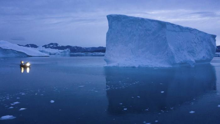 CORRECTING DATE TO 20 - In this Aug. 15, 2019, photo, a boat navigates at night next to icebergs in eastern Greenland. U.S. President Trump announced his decision to postpone a visit to Denmark by tweet on Tuesday Aug. 20, 2019, after Danish Prime Minister Mette Frederiksen dismissed the notion of selling Greenland to the U.S. as