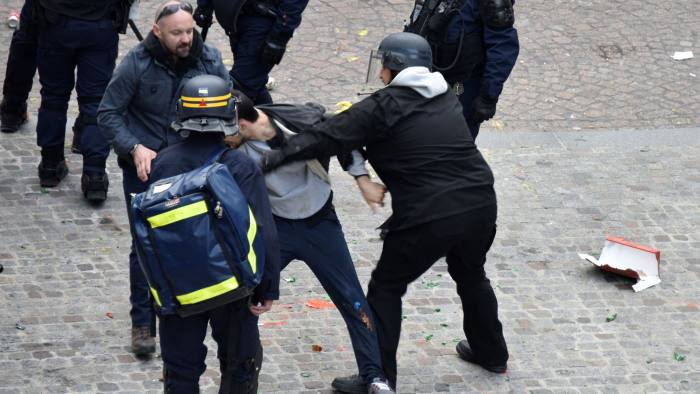 TOPSHOT - This picture taken on May 1, 2018 shows Elysee Chief Security Officer Alexandre Benalla (C) wearing a police visor, next to Vincent Crase (C, left), a security aide for Macron's Republic on the Move party, as they drag away a demonstrator during May 1 protests in Paris. - The most damaging scandal of Emmanuel Macron's presidency deepened on July 21 as his interior minister faces a grilling over his response to a top security aide caught on video striking a young man at a Paris protest in May. Benalla, 26, was initially suspended without pay but on Friday Macron fired his former security aide, who was taken into custody suspected of unlawfully receiving police surveillance footage in a bid to clear his name. He is to face a magistrate on July 22, 2018, Paris prosecutors said. (Photo by Naguib-Michel SIDHOM / AFP)        (Photo credit should read NAGUIB-MICHEL SIDHOM/AFP/Getty Images)