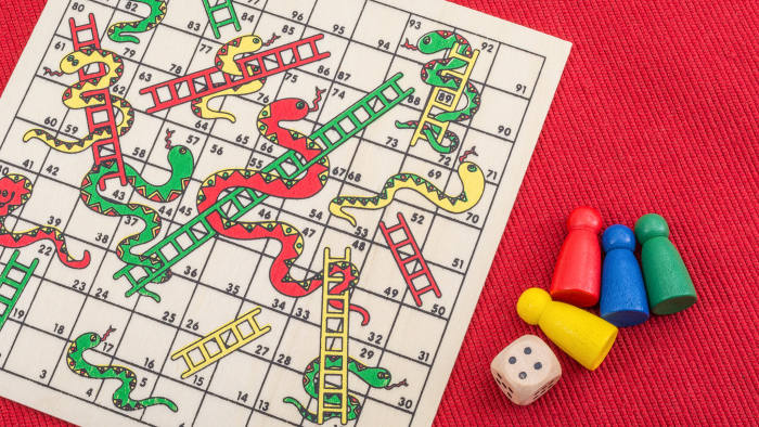 RXFY1H Close-ups of small Snakes and Ladders board game. Metaphor for climbing the career ladder, getting on the housing ladder, social climbing, striving.