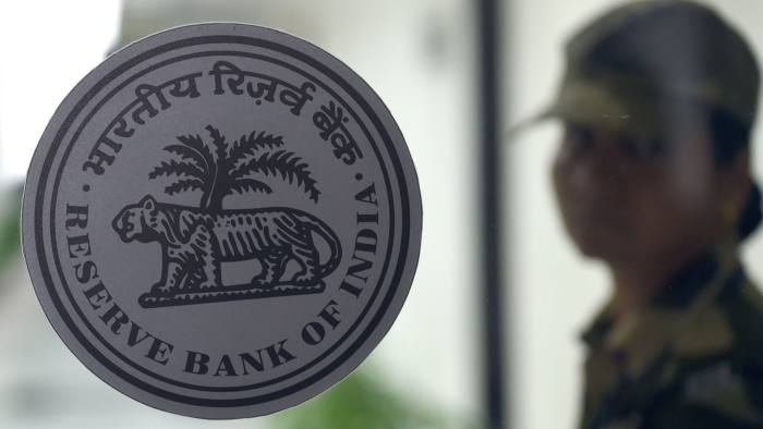 A security staff stands behind a logo of the Reserve Bank of India (RBI) as Governor Urjit Patel addresses a news conference at the bank's head office in Mumbai on December 5, 2018. - India's central bank kept interest rates unchanged on December 5 after Asia's third-largest economy slowed ahead of elections next year. (Photo by Indranil MUKHERJEE / AFP)INDRANIL MUKHERJEE/AFP/Getty Images