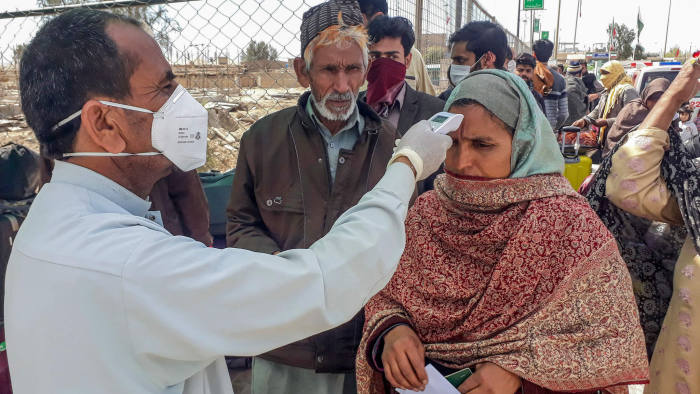 A health personnel checks the body temperature of a pilgrim returning from Iran via the Pakistan-Iran border town of Taftan on February 29, 2020. - Health officials in Pakistan are screening hundreds of people who had recently arrived from Iran, a major new hotspot for coronavirus, after Islamabad this week confirmed its first two infections. (Photo by STRINGER / AFP) (Photo by STRINGER/AFP via Getty Images)
