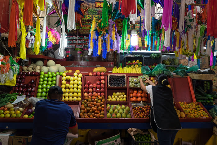 An employee arranges packages of grapes for sale at a stall in the Mercado de San Juan in Mexico City, Mexico, on Friday, Dec. 2, 2016. The National Institute of Statistics and Geography is scheduled to release Mexico's Consumer Price Index (CPI) figures on December 8. Photographer: Cesar Rodriguez/Bloomberg