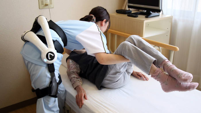 JAPAN-TECHNOLOGY-ROBOT-HEALTH-ELDERLY...A care worker at the Fuyoen nursing home for elderly people, wearing the nursing version of Japanese robot venture Cyberdyne's robot suit Hybrid Assistive Limb (HAL), lifts an elderly woman during a demonstration in Yokohama, suburban Tokyo on June 12, 2015. Kanagawa prefecture government provided 3 HAL robot suits to each of the prefecture's 30 nursing homes to reduce burdens of care workers. The HAL, developed by University of Tsukuba professor Yoshiyuki Sankai, is designed to learn the user's motion and assist their movements. AFP PHOTO / Yoshikazu TSUNO (Photo credit should read YOSHIKAZU TSUNO/AFP/Getty Images)
