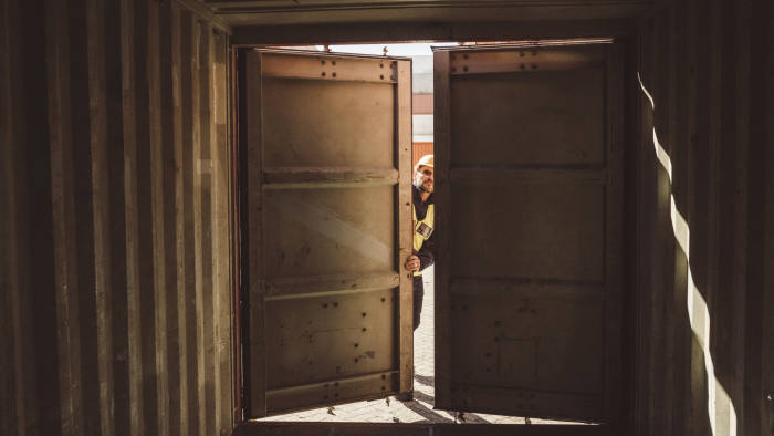 A photo of male port worker opening shipping container. Interior of empty storage compartment. Man is working at shipping yard.